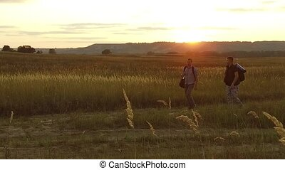 two tourists nature silhouettes. two tourists go at sunset. tourist silhouette nature slow motion video