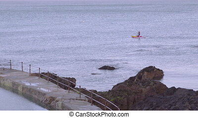 Two tourists paddling their boat in the sea water