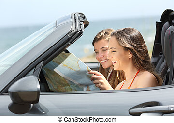 Two tourists reading a map in a convertible car