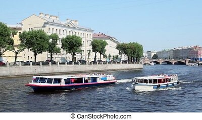 Two tourists ships float by Fontanka river in Petersburg city