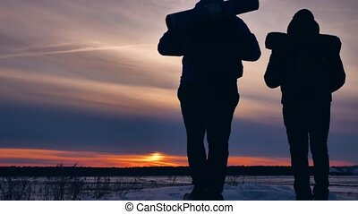 two tourists silhouette travel at sunset climb the mountain...