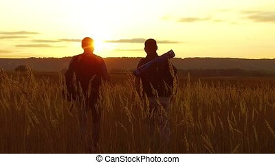 two tourists silhouettes. two tourists go at sunset. tourist nature silhouette nature slow motion video