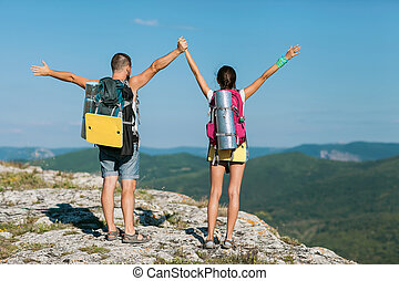 two tourists stand on the mountain