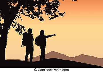 Two tourists standing under a tree pointing in the distance in mountain landscape with orange sky and space for your text