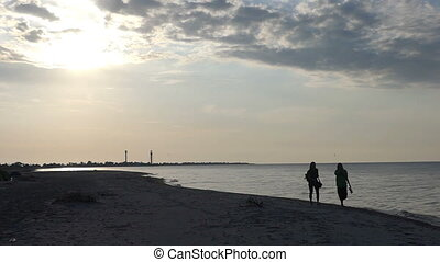 Two tourists walk on the Black Sea beach at sunset