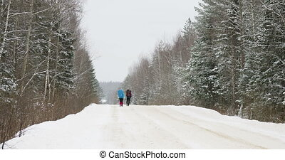 Two tourists with backpacks go on a snow-covered road through the winter forest. Russia.