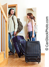 Two tourists with luggage near door in home
