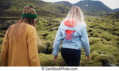 Two tourists woman walking through the lava field in Iceland...