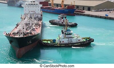 two towing boats rotates tanker in sea port