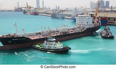 two towing boats turning tanker in sea port