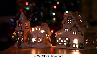 Two toy house-candlestick stand at background of christmas tree ornaments