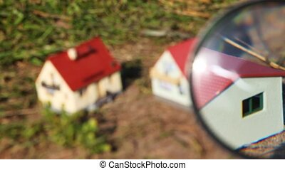 two toy houses are looked through by magnifying glass in park
