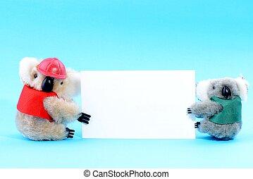Two toy koala holding a blank white card