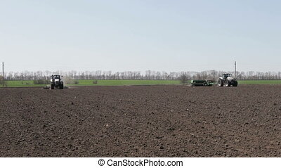 Two tractor with plow and drill going on the black earth's...