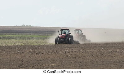 Two tractors going in opposite direction and cultivating...