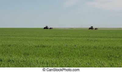 Two tractors on green farm field
