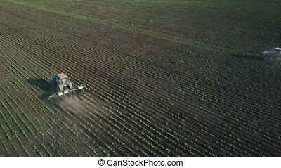 Two tractors performs seeding on the field (top view from...