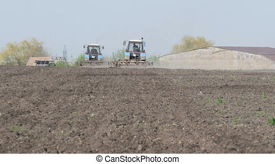 Two tractors work in field in early spring - Two tractors...