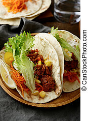 Two traditional Mexican Tacos on a wooden plate