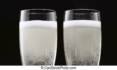 Two transparent glass of chilled champagne. Bokeh blinking black background. Close up
