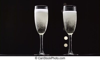 Two transparent glass of chilled sparkling wine. Bokeh blinking black background