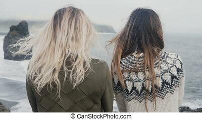 Two traveling women standing on the black beach, bear troll...