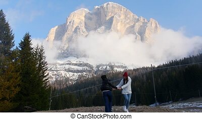 Two traveling young women standing on a background of a mountains and having fun