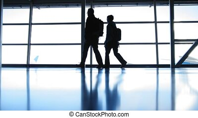 Two travellers going in airport in front of window opposite the runway, silhouette