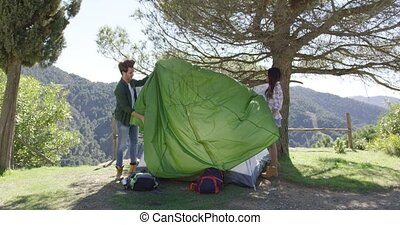 Two travellers putting up tent - Young couple putting up...