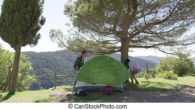 Young couple putting up tent under trees in shadow with beautiful view of on background.