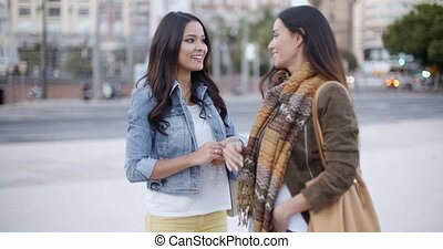 Two trendy young woman chatting in the street