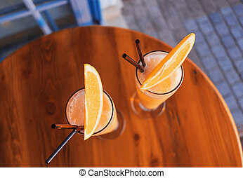 Two tropical cocktails adorned by fresh orange and brightly lit by setting sun on the wooden table of a seafront mediterranean cafe. Flat lay style.