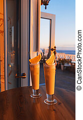 Two tropical cocktails adorned by fresh orange and brightly lit by setting sun on the wooden table of a seafront mediterranean cafe.