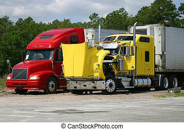 Two 18-wheeled trucks, one yellow, one red, stopped for maintenance. Yellow truck's hood is open.