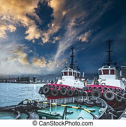 Two tugboats in the port at sunset