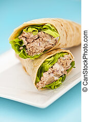 Two tuna melt wrap on a white plate on a blue background
