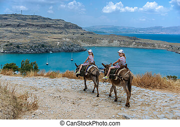 Two twin girls riding donkeys on a mountain road to the sea. Rhodes. Greece