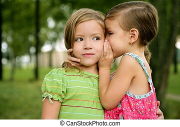 Two twin little sister girls whisper in the ear, outdoor on green park