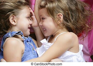 Two twin sisters in a hug, close up