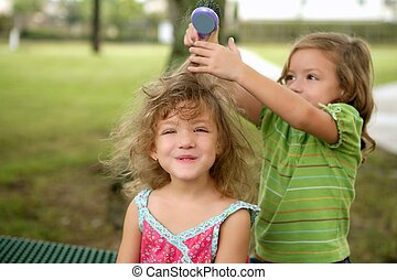 Two twin sisters pretending to be hairdresser