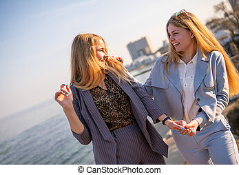 Two Twin teenage girls young woman laughting and having fun near the sea at sunset time