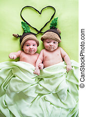 two twins brothers babies weared in acorn hats