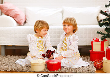 Two twins girls sitting with presents near Christmas tree