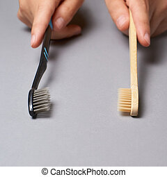 Two hands holding different types of toothbrushes. Plactic and eco bamboo brush. Black and light color or grey background