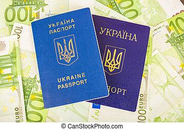 Two Ukrainian passports on euro banknotes