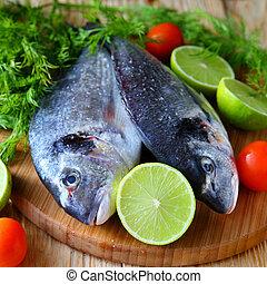 two uncooked fish dorado on board, food closeup
