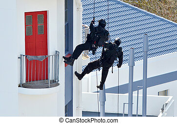 Counter-terrorism police officers abseiling a building - Two...