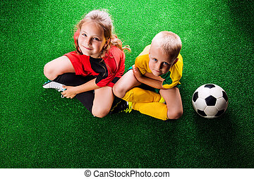 Two unrecognizable little football players against green grass