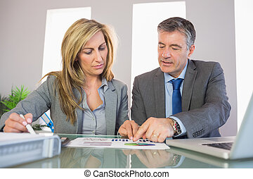 Two unsmiling mature business people pointing at a graphic at office