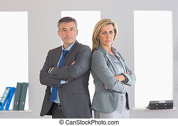 Two unsmiling mature businesspeople looking seriously at camera standing firmly back to back with crossed arms at office